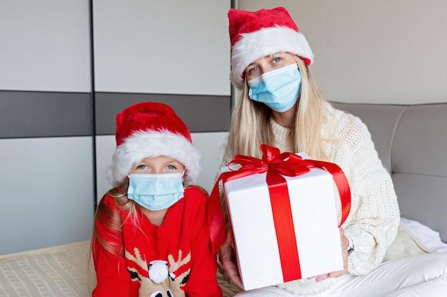 Gelukkige moeder en dochter in medische de giftdoos van de maskerholding. online kerstviering Premium Foto