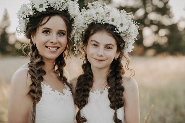 Gelukkige moeder en dochter in witte jurken met bloemenkransen en boho-stijl vlechten in de zomer in een veld Premium Foto