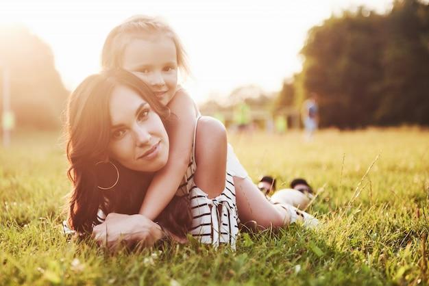 Gelukkige moeder en dochter knuffelen in een park in de zon op een heldere zomer van kruiden. Gratis Foto