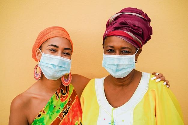 Gelukkige moeder en dochter met traditionele afrikaanse kleding die beschermend gezichtsmasker draagt Premium Foto