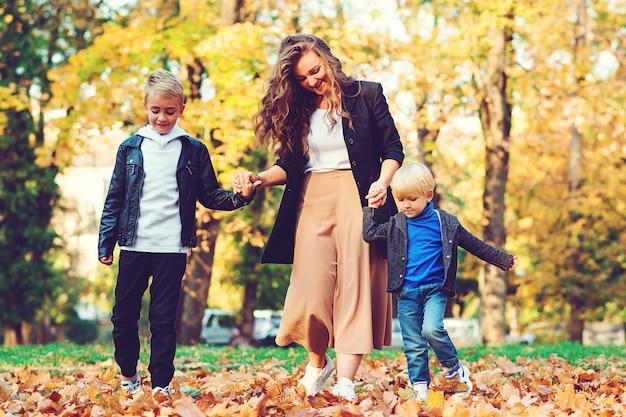 Gelukkige moeder en kinderen plezier buitenshuis. modieuze familie wandelen in herfst park. Premium Foto