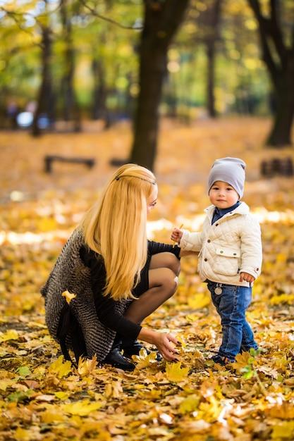 Gelukkige moeder en zoon spelen in het herfstpark Gratis Foto