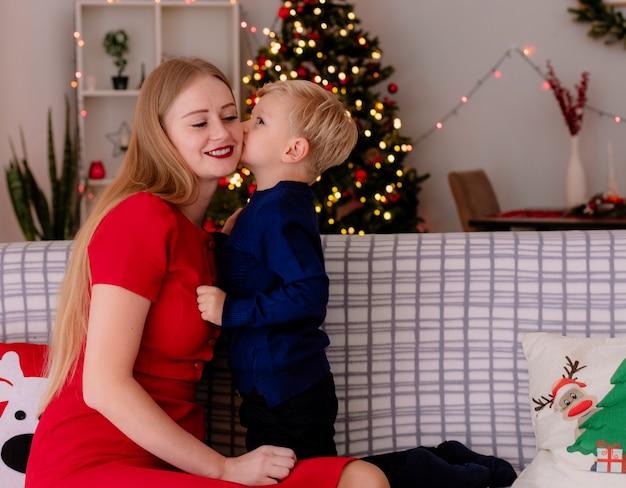 Gelukkige moeder in rode jurk met haar kleine kind zittend op een bank klein kind kuste haar vrolijke moeder in een ingerichte kamer met kerstboom op de achtergrond Gratis Foto