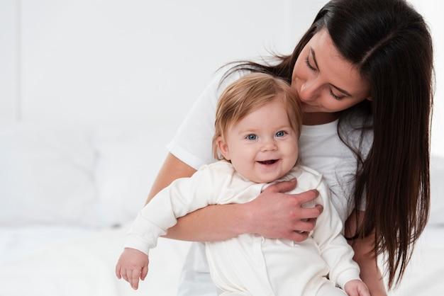 Gelukkige moeder kussende baby Gratis Foto