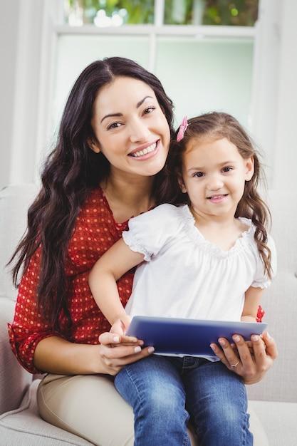 Gelukkige moeder met dochter die een digitale tablet thuis houdt Premium Foto