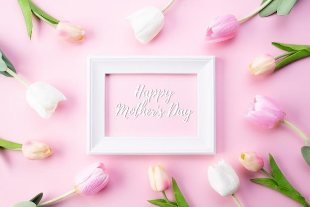 Gelukkige moederdag concept. hoogste mening van roze tulpenbloemen en witte omlijsting Premium Foto