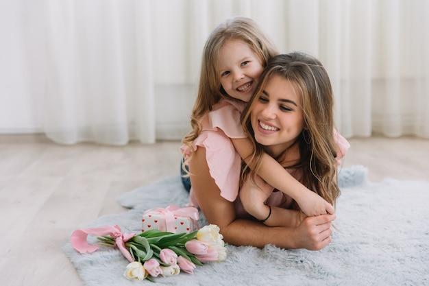 Gelukkige moederdag. kind dochter feliciteert moeder en geeft haar bloemen tulpen en cadeau Premium Foto