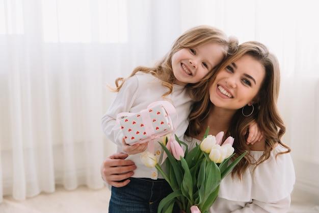 Gelukkige moederdag. kind dochter feliciteert moeders en geeft haar bloemen tulpen en cadeau. Premium Foto
