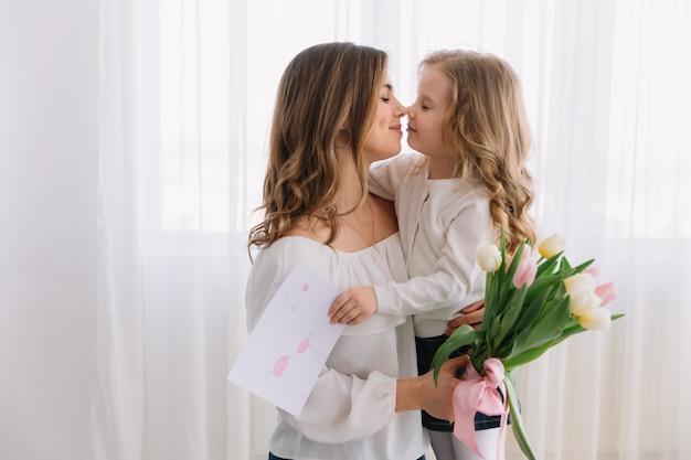Gelukkige moederdag. kind dochter feliciteert moeders en geeft haar een briefkaart en bloemen tulpen. Premium Foto