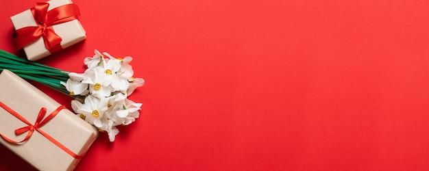 Gelukkige moederdagtekst en mooie rode tulpen met giftvakje op rode achtergrond. Premium Foto