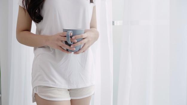 Gelukkige mooie aziatische vrouw die en een kop van koffie of thee glimlacht drinkt dichtbij het venster in de slaapkamer. Gratis Foto