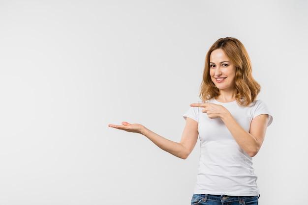 Gelukkige mooie jonge vrouw die op iets op hand richt Gratis Foto