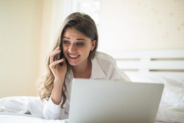 Gelukkige mooie vrouw die aan laptop op het bed in het huis werkt Gratis Foto