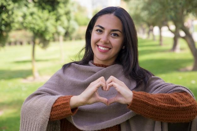 Gelukkige mooie vrouw die hartgebaar in stadspark maakt Gratis Foto