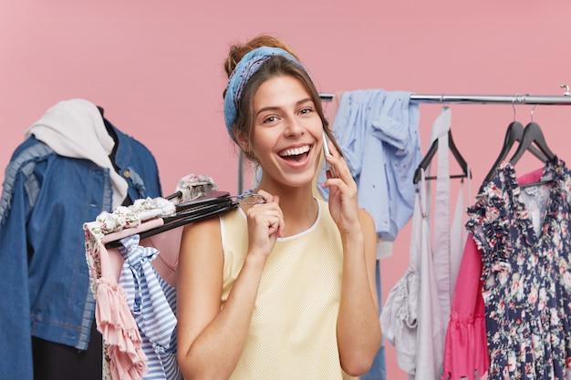 Gelukkige mooie vrouw die winkeldag heeft, veel kleren kiest om te kopen, een gesprek met iemand heeft via smartphone, breed lacht, verheugt zich over grote kortingen in de winkel en een goede aankoop Gratis Foto