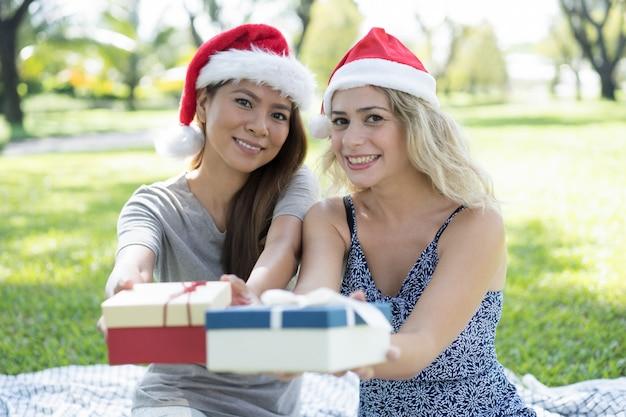 Gelukkige mooie vrouwen die kerstmanhoeden dragen en giftdozen geven Gratis Foto