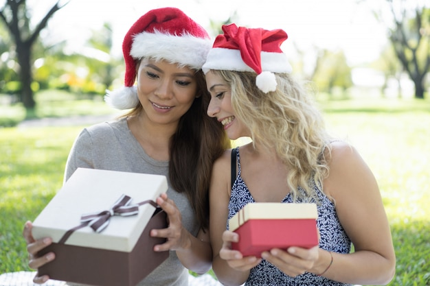 Gelukkige mooie vrouwen die kerstmanhoeden dragen en in giftdoos piepen Gratis Foto
