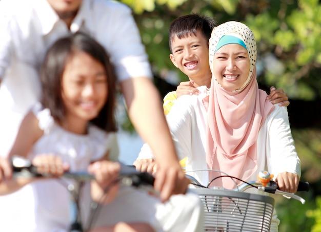 Gelukkige moslim familie fietsen Premium Foto
