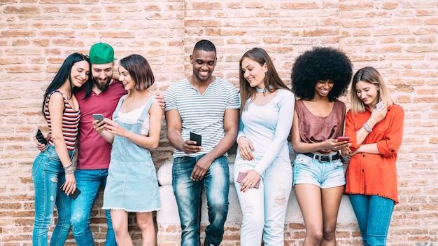 Gelukkige multi-etnische vrienden die smartphone gebruiken bij universitaire universiteitsbinnenplaats Premium Foto