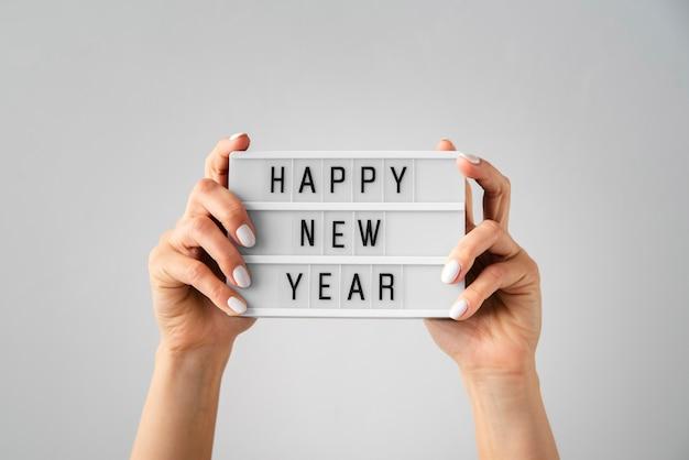 Gelukkige nieuwe jaarkaart die in handen wordt gehouden Gratis Foto