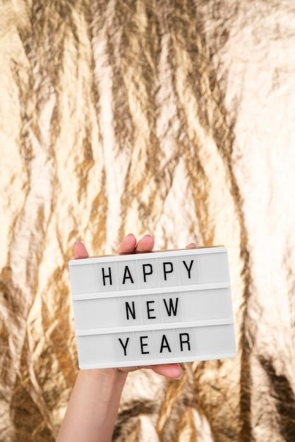 Gelukkige nieuwe jaarplaat met vage gouden achtergrond Gratis Foto