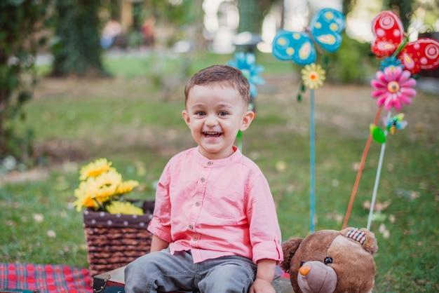 Gelukkige ondergeschikte babyjongen in de tuin op een zonnige dag Premium Foto