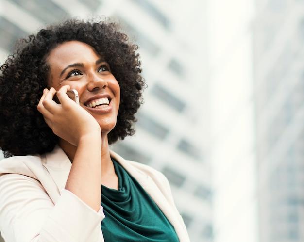 Gelukkige onderneemster die op de telefoon spreekt Gratis Foto