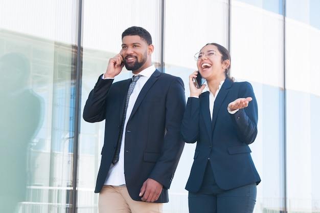Gelukkige opgewekte bedrijfscollega's die van grappige telefoonbesprekingen genieten Gratis Foto
