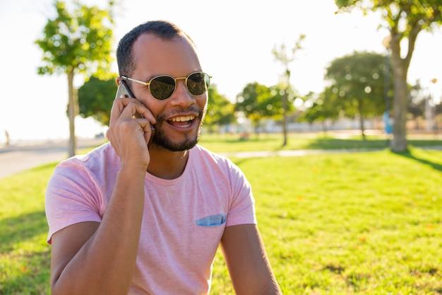 Gelukkige opgewekte latijnse kerel die in zonnebril op mobiele telefoon spreekt Gratis Foto