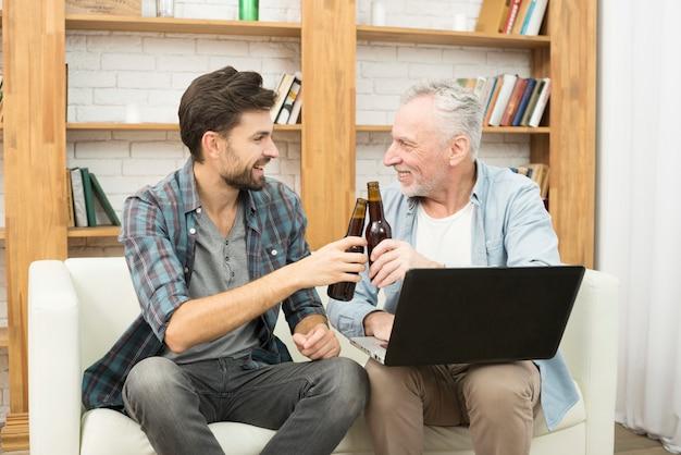 Gelukkige oude man en jonge kerel rinkelende flessen en het gebruiken van laptop op bank Gratis Foto