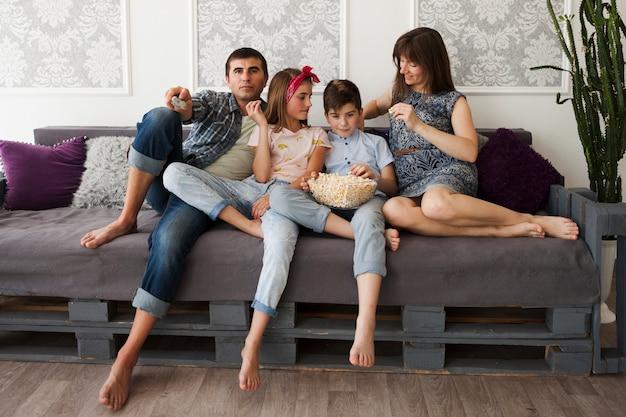 Gelukkige ouder met hun kinderen die op bank zitten en popcorn eten Gratis Foto