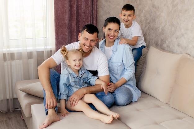 Gelukkige ouders chatten met hun kinderen thuis, samen op de bank in de woonkamer zitten en glimlachen Premium Foto