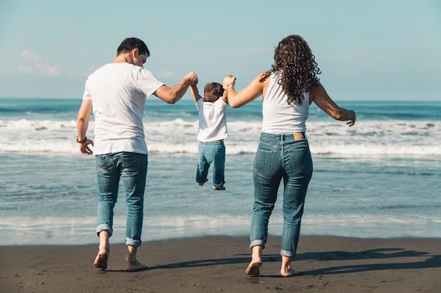 Gelukkige ouders die hun baby op zonnig strand werpen Gratis Foto