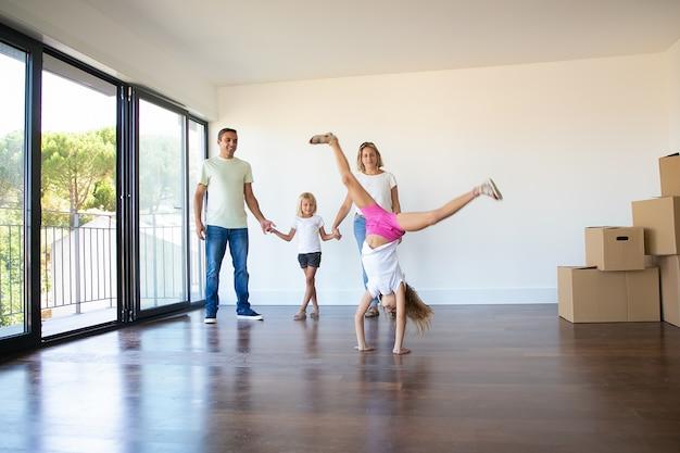 Gelukkige ouders en dochters die housewarming vieren, meisje doet radslag Gratis Foto