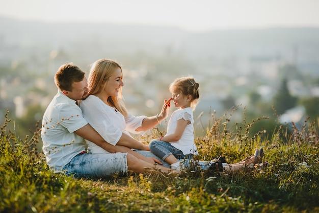 Gelukkige ouders en hun kleine meisje rusten op het gazon in mooie zomerdag Gratis Foto
