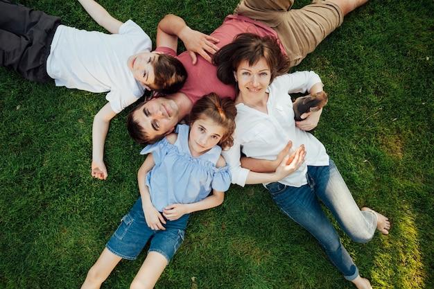 Gelukkige ouders en kinderen liggen op gras in het park Gratis Foto