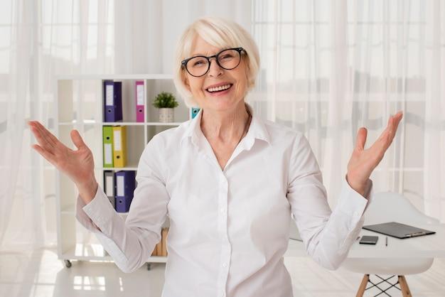 Gelukkige oudste in haar kantoor medium schot Gratis Foto