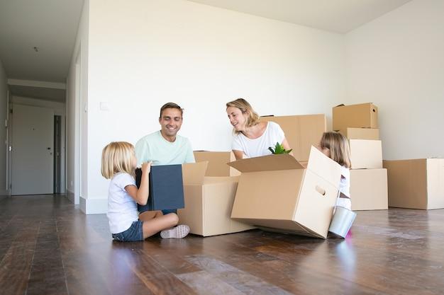 Gelukkige paar en twee meisjes verhuizen naar een nieuw leeg appartement, zittend op de vloer in de buurt van open dozen Gratis Foto
