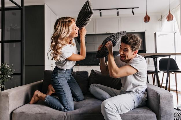 Gelukkige paar genieten van kussengevecht. blij meisje speelt met vriendje in de woonkamer. Gratis Foto
