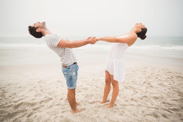 Gelukkige paar hand in hand op het strand Premium Foto