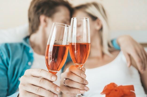 Gelukkige paar het drinken wijn in de slaapkamer Gratis Foto