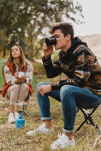 Gelukkige paar in het bos die koffie drinken Gratis Foto