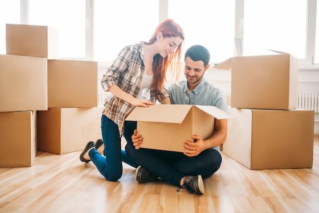 Gelukkige paar kartonnen dozen uitpakken met eigendom, housewarming. verhuizen naar een nieuw huis Premium Foto
