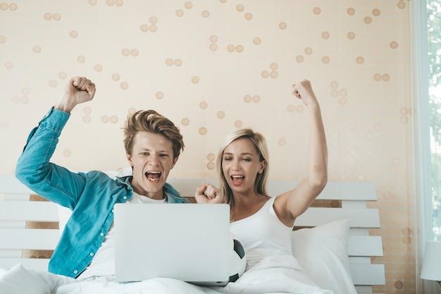 Gelukkige paar kijken naar voetbal voetbal op het bed Gratis Foto