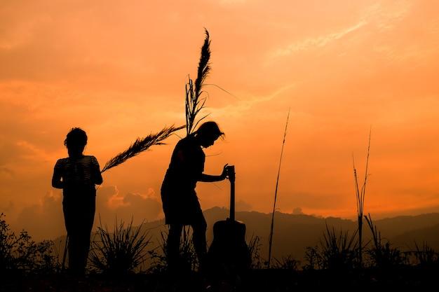 Gelukkige paar kinderen spelen op weide bij zonsondergang, silhouet Premium Foto