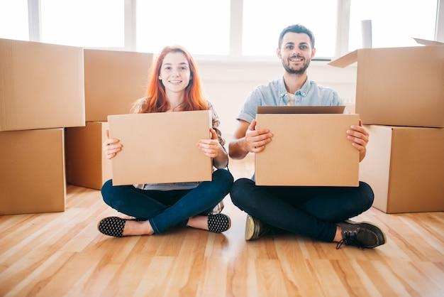 Gelukkige paar met kartonnen dozen in handen zittend op de vloer, verhuizen naar nieuw huis, housewarming Premium Foto