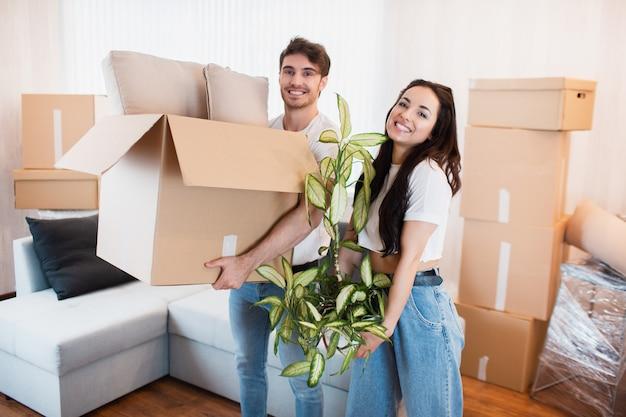 Gelukkige paar met kartonnen dozen in nieuw huis op bewegende dag. Premium Foto