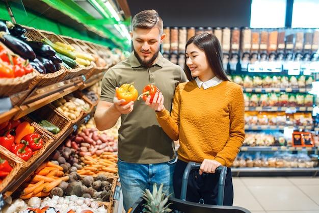 Gelukkige paar met mand in de supermarkt Premium Foto
