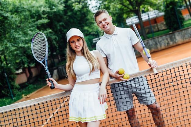 Gelukkige paar na het spelen van tennis op de baan. portret van glimlachende jonge man en mooie vrouw met tennisrackets. Premium Foto
