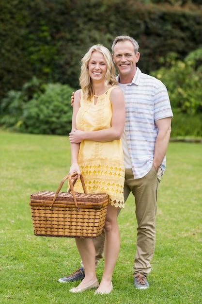 Gelukkige paar picknickmand buiten te houden Premium Foto